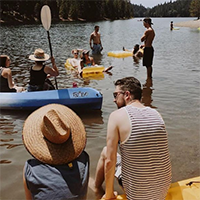 """people sitting on kayaks and canoes on a river in california"""