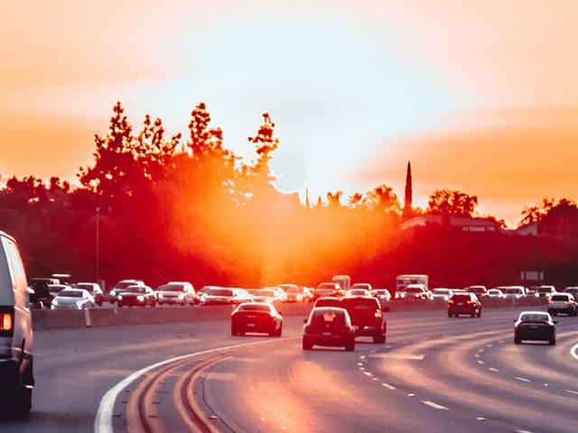 cars on a highway during the sunset